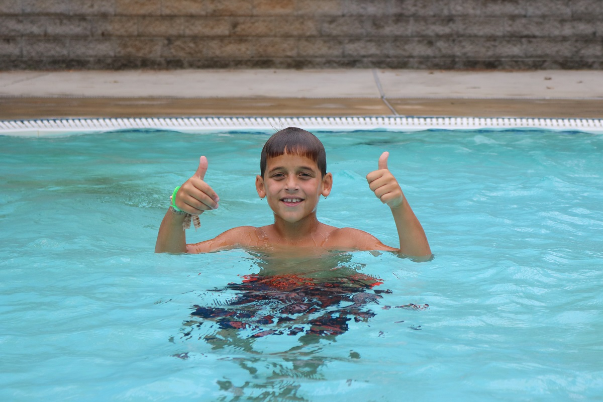 boy in pool at Camp Wannaklot giving two thumbs up