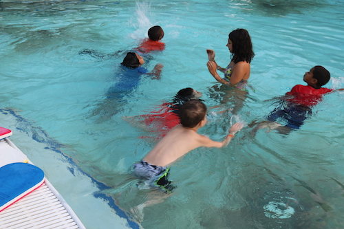 group of kids in pool learning to swim