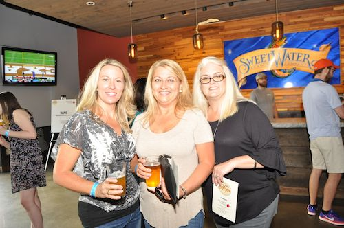 3 blond women in front of the sweetwater beer flag
