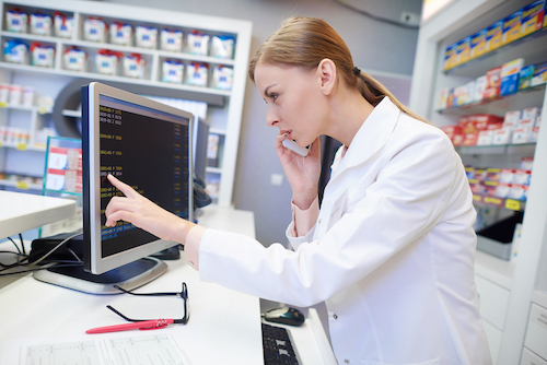 Pharmacist reviewing order on computer
