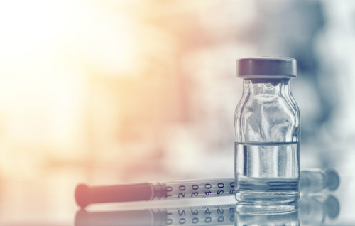 Medicine bottle and needle on desk